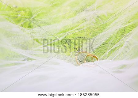 wedding rings and bouquet of chrysanthemums on a white veil
