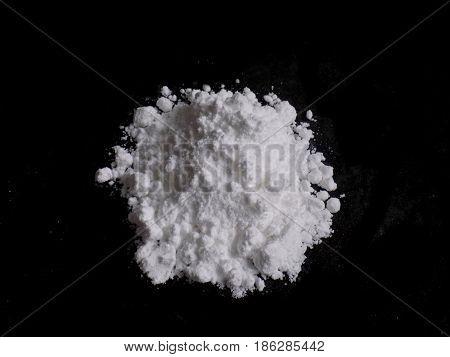 Cocaine drug powder pile on black background