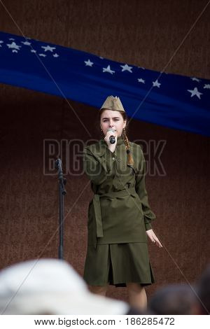 MARGANETS UKRAINE - MAY 9 2017: Young unknown actress in old military uniform reads poetry while open concert dedicated to celebrating 72th anniversary of Victory in the Second World War on 9th of May 2017 in Marganets Ukraine