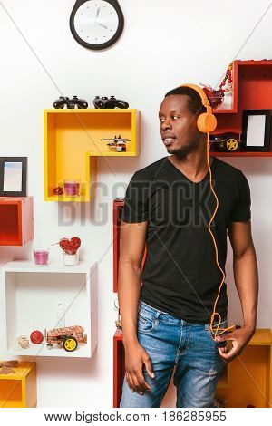 Young afroamerican meloman man in bright orange headphones listen favorite music at home. Fun, leisure, hobby, creativity concept.