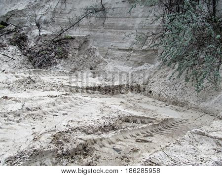 Background of the Sand quarry. A wall of white sand and traces of Machines that came to collect its