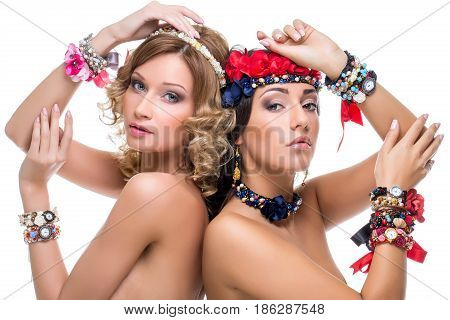 Beautiful blond and brunette young women with many ribbon headbands and bracelets. Beauty shot on white background. Isolated. Copy space.