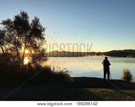 Nature and landscape photographer photographing at sunrise Lake Rotorua in the centre of the North Island of New Zealand.