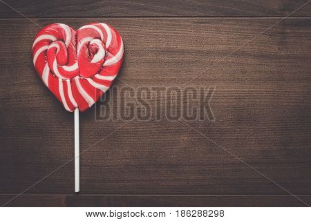 red sugar heart-shaped lollipop on the wooden table. heart-shaped lollipop on the brown table. heart-shaped lollipop on wooden background. heart-shaped lollipop background with copy space