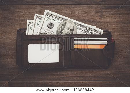 men's wallet with money in it. wallet with credit and debit cards. money in wallet on the brown table. wallet on wooden background with copy space. brown leather opened wallet