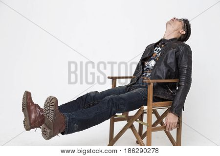 Man in a leather jacket photo in the studio the man is sitting in the director's chair after shooting the film rest