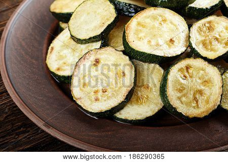 Fried zucchini in a clay plate on a wooden table. vegetarian meal on a wooden table space for text