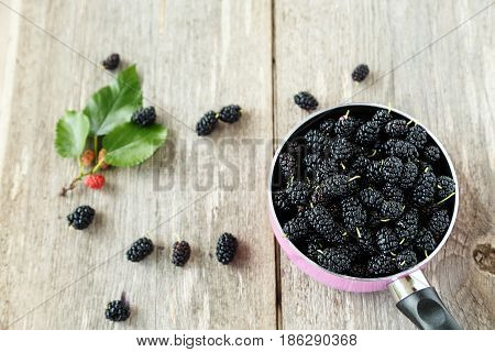 black mulberry berries in a pink pot on a wooden table. in the foreground are mulberry berries and sprig with ripened berries.