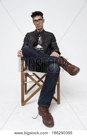 Man in a director's chair on a white background in the studio a man in a black leather jacket jeans and glasses. modern film art