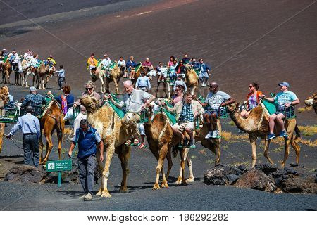 Timinfaya National Park, Lanzarote Island, Spain - March 30, 2017: Tourists Riding Camels In Timanfa