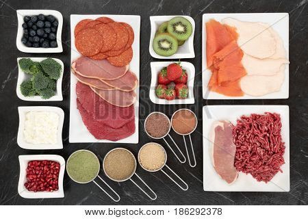 Body building food with meat, fish, supplement powders, dairy, fruit and vegetables on porcelain plates and in measuring scoops.