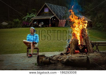 Man traveler relaxing in the forest and looking at the fire. Travel Lifestyle concept vacations outdoor in forest