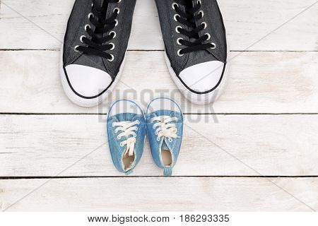 Father and son shoes on white wooden background father's day