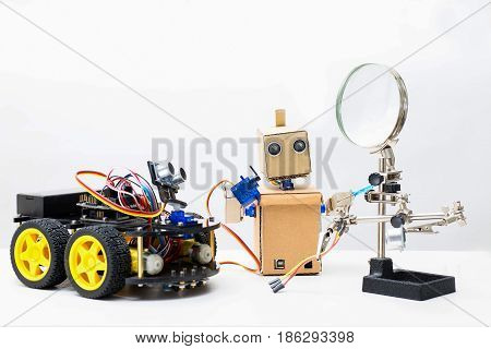 Two robots stand on a table on a white background