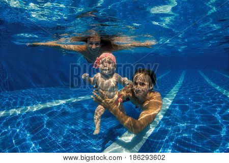 Funny photo of  happy active young family with active baby diving in swimming pool with fun jump deep down underwater.