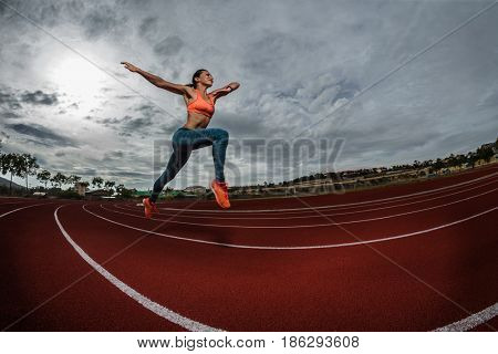 Female sprinter athlete starting a race on a tartan racetrack