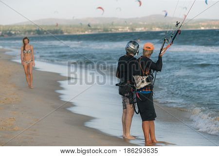 A kite surfer looking at woman on the beach