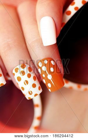White orange manicure with a design of dots on female hand close up.