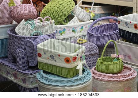 various rattan basket stacked in store. handmade straw woven container colorful