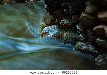 Waterfall and rock with leaf in dark low key and long exposure with copy space
