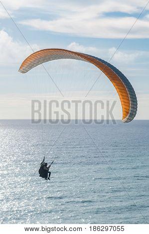 Flying tandem paraglider over the sea, vertical shot.