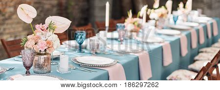 Flower table decorations for holidays and wedding dinner. Table set for holiday, event, party or wedding reception in outdoor restaurant. Banner for website