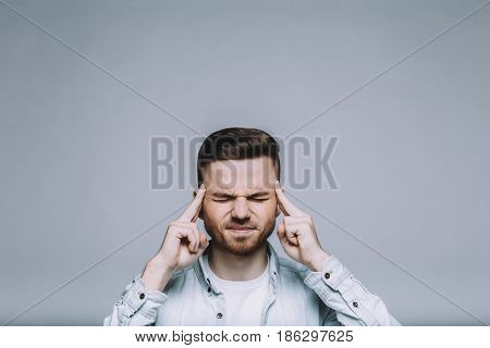 Serious young man with beard in a white shirt having a brain storming. He pressed his forefinger to his temples and deeply thinking about something important. Cut view. Isolated. Close up