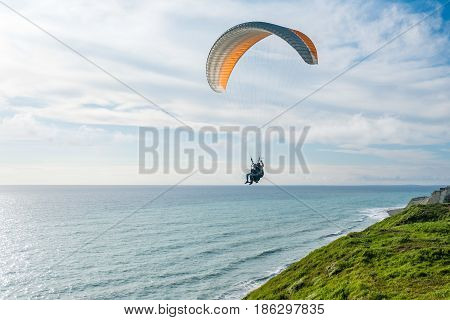 Flying tandem paragliders over the sea and near the mountains, beautiful landscape view.