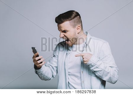 Handsome guy is yelling at somebody or he is angry with video the he has seen or results that he discovered on the mobile phone screen . Profile view from the left side. Close up. Isolated