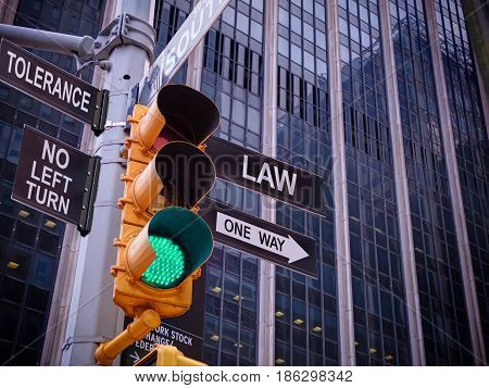 NYC Wall street yellow traffic light black pointer guide one way green light to Law legislation, no turn no way to tolerance to crime. One way to Law and rule. Best choice, right choice. Wall street
