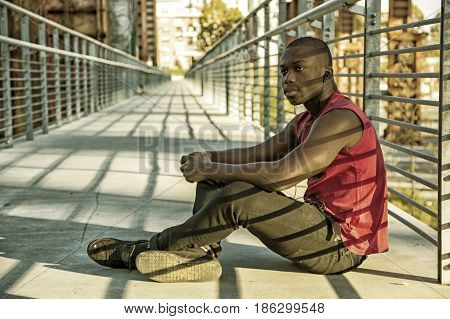 Portrait of a sexy young black man in urban environment wearing red sleeveless shirt, sitting against railing