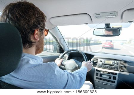 Man driving his car in a sunny day