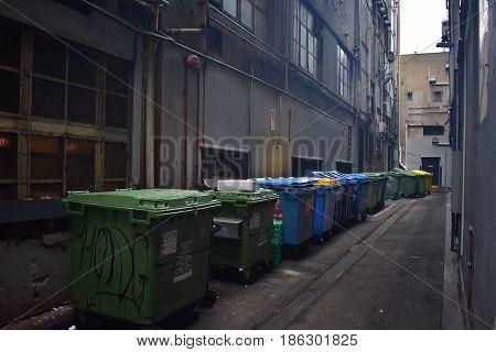 trashcans trash bins in alleyway in urban street