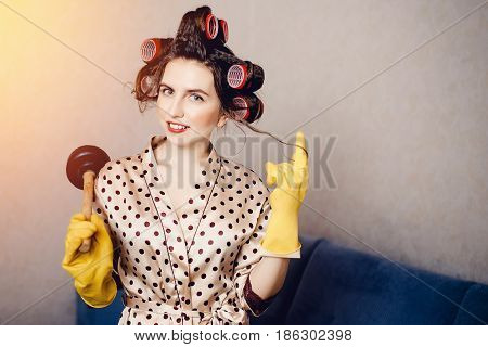 woman with curls on the head of a runner in clothes for home is holding a cleaner to clean the clog in the pipes of the plunger. Concept clean the blockage with their own hands.