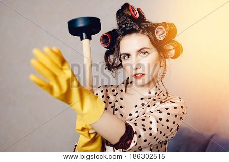 curum hair woman in clothes for the house holds a plunger and puts on a brittle rubber glove. The concept of protecting the skin of hands and nails from breakage and dryness.