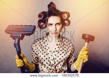 girl with curls on the head of a hair curler holds a plunger and a brush from a vacuum cleaner. Concept cleaning the house with your own hands.