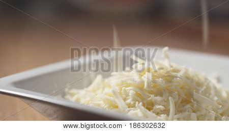 grated pizza mozzarella cheese falls in plate, 4k photo