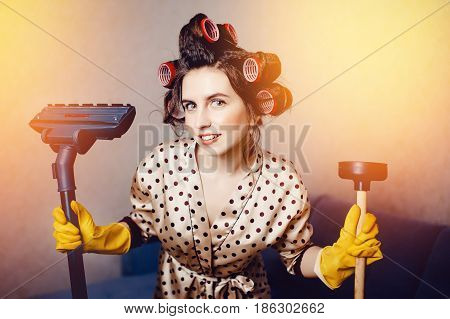 woman with curls on her head in a lace dressing gown keeps a cleaning agent in the pipes and a brush for a vacuum cleaner.concept of cleaning the apartment and the house.