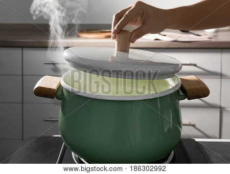 Female hand holding lid above pan in kitchen