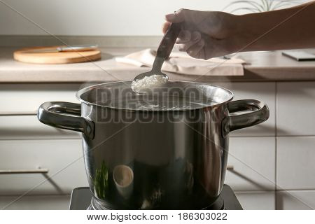 Female hand holding spoon with rice above metal pan on hotplate in kitchen