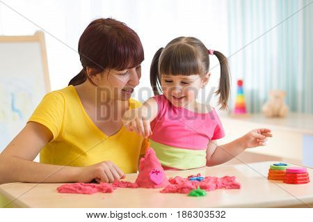 Woman and child play with kinetic sand in kindergarten ot daycare center