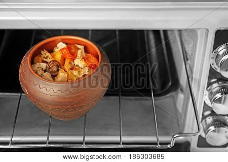 Crock pot with chicken ragout in oven
