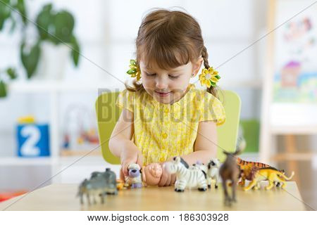 Happy little child plays animal toys at home or daycare centre