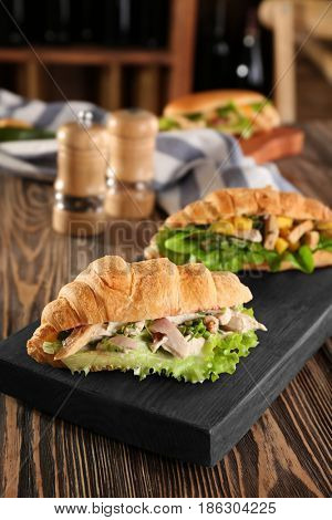 Wooden board with chicken salad in croissant bun on table