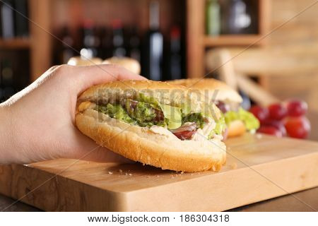 Female hand holding burger bun with chicken salad