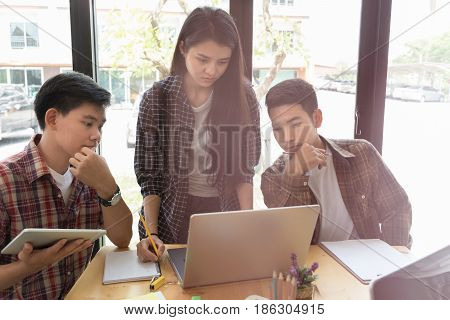 Young University Students Studying With Computer And Tablet In Cafe. Group Of People In Campus Libra
