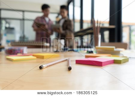 Pencil And Sticky Note On Table With Background Of Young University Students Studying With Tablet Do