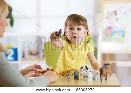 Happy little kid girl. Smiling child toddler playing animal toys at home or kindergarten