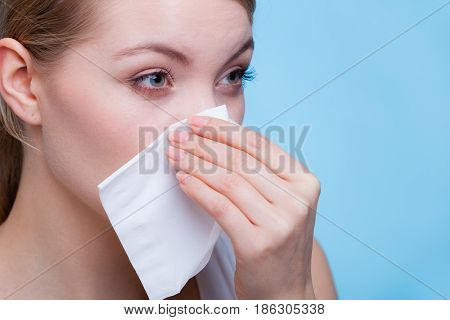 Disease sickness allergy malady problem concept. Woman wiping her nose with hygienic paper tissue having cold and feeling bad.