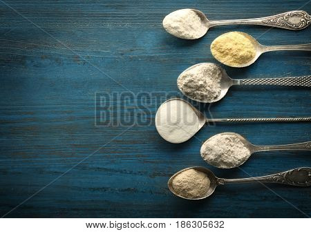 Spoons with different types of flour on grunge wooden background